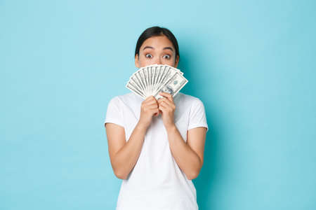 Shopping, money and finance concept. Excited and amused cute asian girl prepared her dollars to pay for concert or awesome product online, holding cash over face and looking amazed