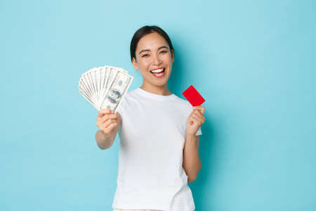 Shopping, money and finance concept. Happy carefree asian girl in white t-shirt holding credit card but choosing cash instead. Dont like contactless payment, smiling upbeat, blue background Фото со стока