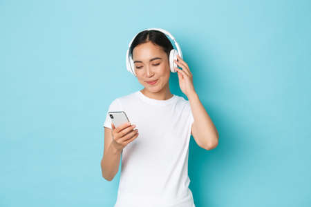 Lifestyle, people and leisure concept. Smiling attractive asian woman picking song in playlist, looking at smartphone screen while deciding what listen in headphones, blue background