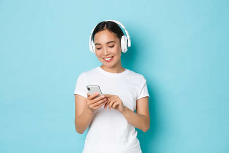 Lifestyle, people and leisure concept. Smiling attractive asian female using wireless headphones and mobile phone, watching video at crowded place, listening music, light blue background Фото со стока