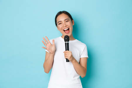 Lifestyle, people and leisure concept. Cheerful smiling asian girl enjoying karaoke night. Japanese female student singing song in microphone with happy emotions, standing light blue background Фото со стока
