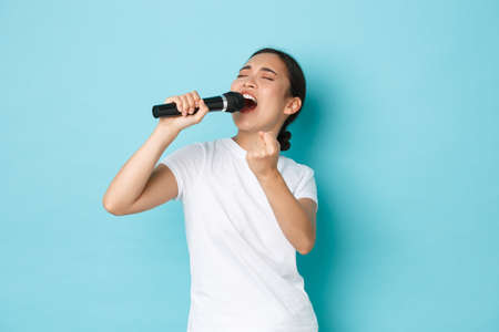 Lifestyle, people and leisure concept. Passionate and carefree pretty asian girl singing song in microphone, bending during performance, like going karaoke, standing light blue background performing Фото со стока
