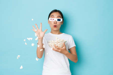 Lifestyle, leisure and emotions concept. Startled asian pretty girl watching movie in 3d glasses, looking at screen astonished and throwing popcorn at TV as beeing surprised with too real picture Фото со стока