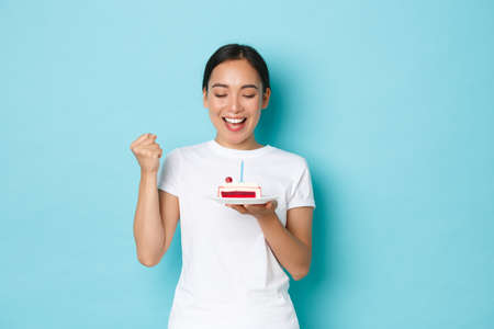Holidays, lifestyle and celebration concept. Satisfied and excited, upbeat asian b-day girl enjoying party, fist pump encourage herself that wish come true, lookng at birthday cake Фото со стока
