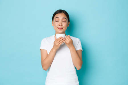 Portrait of delighted dreamy, pretty asian girl in white t-shirt, close eyes and smelling coffee, enjoying morning routine, sipping cappuccino from mug, standing light blue background