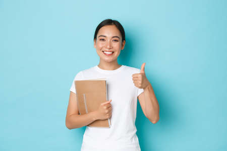 Lifestyle, education and people concept. Portrait of satisfied and happy asian female student in white t-shirt, korean girl showing thumbs-up, carry notebooks, recommend college Фото со стока