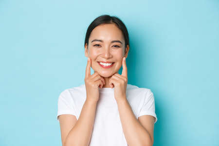 Close-up of beautiful asian girl looking pleased, smiling white teeth, touching cheeks, recommend skincare product, cosmetics for facial skin, standing light blue background Фото со стока