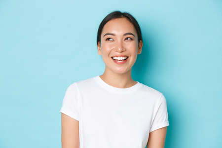 Close-up of dreamy asian girl in white t-shirt, looking hopeful and happy upper left corner, laughing and smiling broadly, standing joyful over light blue background