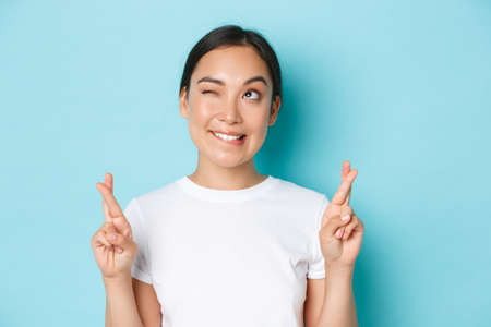 Close-up of hopeful dreamy asian girl making wish, looking upper left corner thoughtful, standing light blue background with fingers crossed for good luck, praying or anticipating positive news
