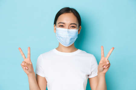Covid-19, social distancing and coronavirus pandemic concept. Cute smiling asian girl in white t-shirt, medical mask, showing peace kawaii geture, staying positive, light blue background