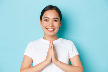 Close-up of pleasant attractive asian girl smiling, holding hands in plead, praying gesture, thanking for something, show namaste sign, standing over light blue background