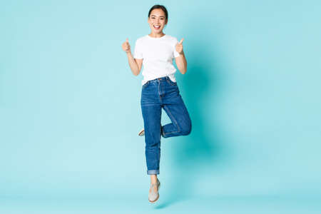 Fashion, beauty and lifestyle concept. Upbeat pretty asian girl in casual outfit, enjoying shopping, jumping from happiness and excitement, showing thumbs-up over light blue background Stock Photo