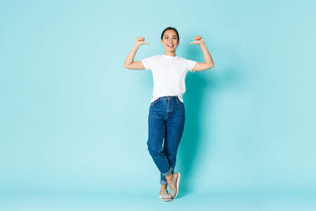 Fashion, beauty and lifestyle concept. Sassy attractive asian girl in casual clothes, pointing at herself, being professional, praising own accomplishment, show-off over light blue background Фото со стока