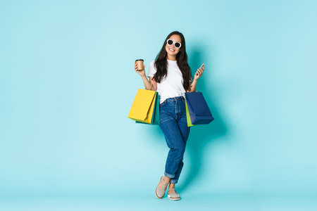 Fashion, beauty and lifestyle concept. Elegant smiling asian woman in sunglasses, holding shopping bags and drinking takeaway coffee during walk in stores, buying things, light blue background