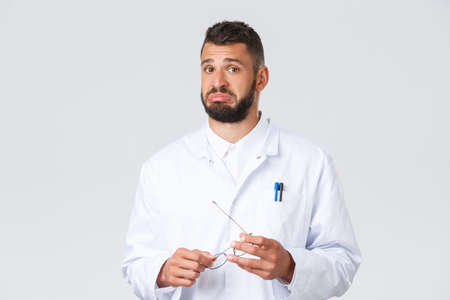 Healthcare workers, coronavirus, covid-19 pandemic and insurance concept. Handsome unsure doctor in medical white coat, hold glasses, pouting indecisive, listen to interesting point view