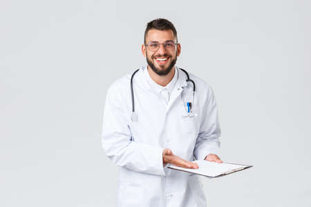 Healthcare workers, medical insurance, clinic lab and covid-19 concept. Cheerful and relieved handsome doctor reveal good results of test screening, smiling patient, point at clipboard