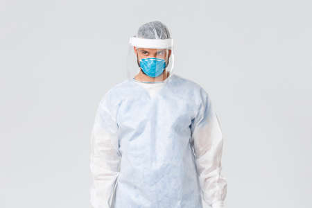 Covid-19 pandemic, virus outbreak, clinic and healthcare workers concept. Serious confident doctor in personal protective equipment, respirator and face shield, look away with determined look