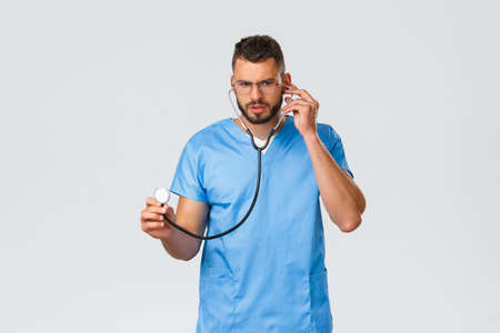 Healthcare workers, medicine, covid-19 and pandemic self-quarantine concept. Serious-looking focused young doctor, physician in ER wearing scrubs, glasses, listening patient lungs with stethoscope Stock fotó
