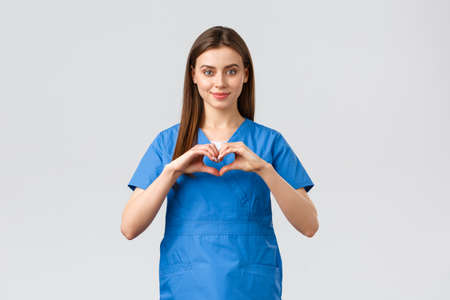 Healthcare workers, prevent virus, insurance and medicine concept. Smiling attractive female doctor, nurse in blue scrubs stay safe home, show heart sign, express respect to coronavirus fighters