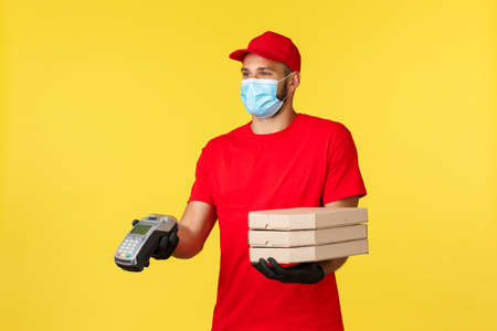 Food delivery, tracking orders, covid-19 and self-quarantine concept. Smiling friendly courier in medical mask and red uniform, giving clients payment terminal and pizza, contactless paying for order