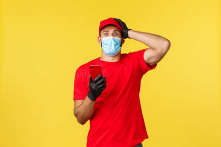 Food delivery, tracking orders, covid-19 and self-quarantine concept. Worried and nervous courier in red uniform and medical mask, touch head anxious, holding smartphone, read intimidating news