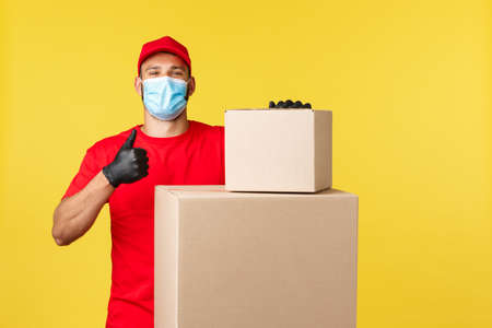 Express delivery during pandemic, covid-19, safe shipping, online shopping concept. Proud and confident courier assure packages are safe, thumb-up as stand near boxes with parcels