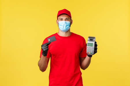 Food delivery, tracking orders, covid-19 and self-quarantine concept. Courier in red uniform, medical mask and gloves, showing POS terminal and credit card, contactless paying during coronavirus 写真素材