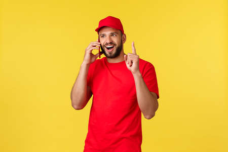 Contactless payment, online delivery, internet shopping and parcel tracking concept. Enthusiastic young employee, male courier in red uniform, raise finger as talking phone, have suggestion 写真素材