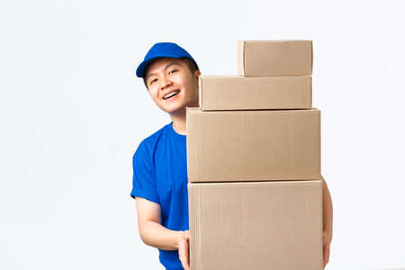 Online shopping, fast shipping concept. Smiling happy asian delivery man in blue courier uniform, looking behind boxes with client orders, carry parcels to client home, white background