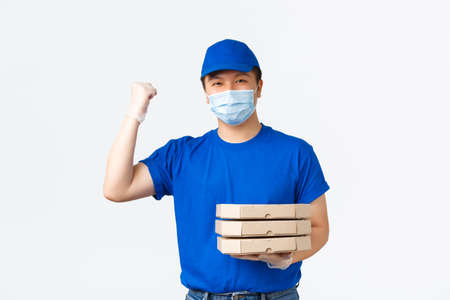Contactless delivery, covid-19 shipping, preventing virus concept. Excited asian courier in medical mask and gloves, blue uniform, raising hand in hooray, triumph, bring pizza order to client home