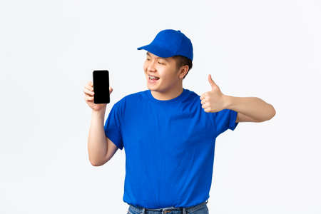 Technology, online shopping and shipping concept. Smiling pleased asian delivery man in blue uniform, showing thumbs-up and looking satisfied at mobile phone screen, recommend app, white background