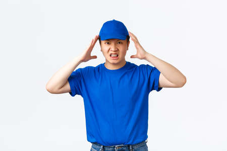 Pissed-off and angry asian delivery man in blue uniform shaking hands near head, grimacing mad and outraged. Courier looking distressed, tired of rude customers, standing white background Stock Photo