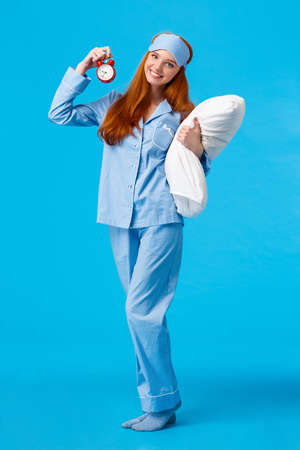 Vertical full-length cheerful lovely, gentle redhead european woman with long red hair, wearing nightwear and sleep mask, holding pillow and red alarm clock, sweet dreams