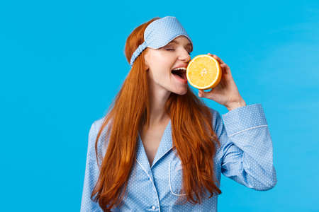 Delicious fruit starting morning healthy. Waist-up portrait attractive sleepy, pretty redhead girl in sleep mask and nightwear, biting slice of orange eating tasty, standing blue background