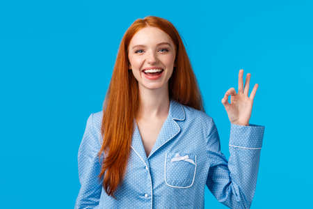 Cheerful and relieved smiling happy redhead girl in nightwear, ready sleep showing okay gesture like or approval, give positive reply, standing blue background