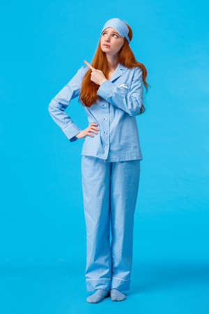 Uneasy and worried, concerned upset redhead female in nightwear and sleep mask, looking pointing upper left corner sad and distressed facing hard choice, standing troubled blue background