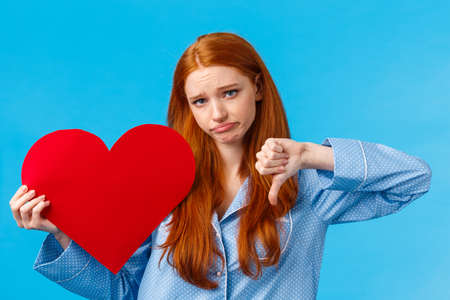 Upset and disappointed gloomy redhead girl in pyjama was rejected feeling uneasy and depressed, showing thumb-down dislike and heart card, valentines day concept. blue background