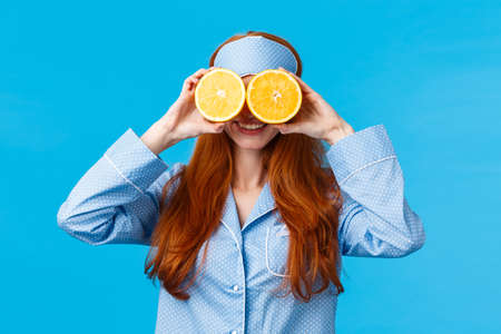 Carefree pretty and cute redhead woman in nightwear, sleep mask, holding two slices of orange over eyes and smiling, fool around in morning, standing blue background joyful