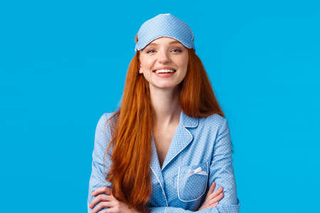 Assertive and confident good-looking optimistic redhead girl ready go bed, wearing sleep mask and cute nightwear, hold hands crossed chest like professional, self-assured pose, blue background
