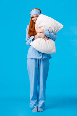 Silly romantic and cute, gentle young redhead coquettish woman in pyjama and sleep mask, hugging pillow peeking at camera with tender lovely smile, standing over blue background