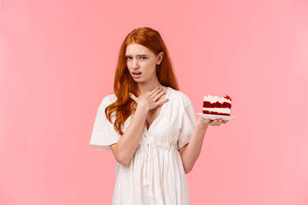 express aversion and disappoinment, touching neck as willing puke from awful tasty. Ignorant redhead female attend friends b-day party holding plate with cake, show disgust