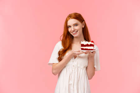 Lovely, romantic and alluring redhead girlfriend baked delicious surprise for valentines day date, holding peace cake on plate and smiling tempting with sassy, coquettish expression, pink background