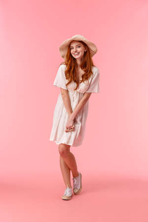 Full-length vertical shot silly, coquettish caucasian redhead woman on romantic date, blushing looking flirty and giggle at camera, enjoying perfect company, great day, stand pink background
