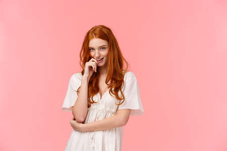 Sensual, romantic and sassy, seductive redhead daring woman in white dress, biting finger and coquettish look camera from under forehead, standing pink background, flirting