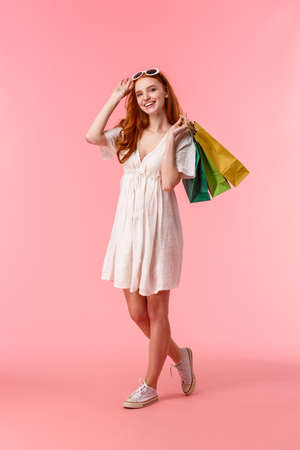 Full-length vertical shot delighted, relaxed and carefree female shopaholic, enjoy walking shopping mall, buying things with discounts, holding shop bags, smiling, take-off sunglasses Banco de Imagens