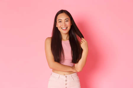 Lifestyle, beauty and women concept. Portrait of stylish carefree asian girl playing with hair while talking, smiling pleased, having lively conversation with girlfriends over pink background