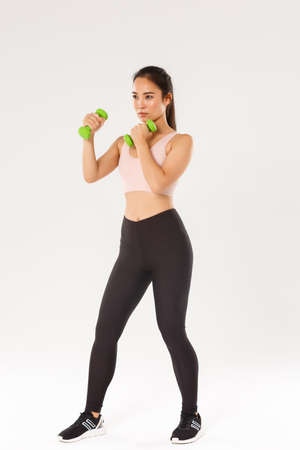 Sport, gym and healthy body concept. Full length of serious-looking asian brunette sportswoman, female athlete in sports bra and leggings lifting dumbbells, fitness exercises over white background