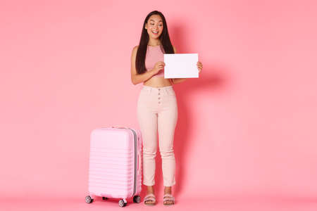 Travelling, holidays and vacation concept. Full-length of coquettish trendy brunette asian girl waiting for someone to pick her up airport, standing with sign and suitcase over pink background