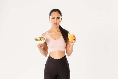 Sport, wellbeing and active lifestyle concept. Sulking and reluctant cute asian girl hates eating healthy, holding salad and orange juice with annoyed pouting face, hate being on diet and workout