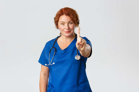 Medicine, healthcare and coronavirus concept. Smiling female middle-aged doctor, medical worker in scrubs shaking finger in warning or disapproval, prohibit something, restrain from action Stock Photo